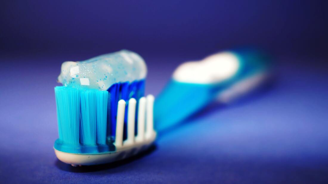toothbrush with whitening toothpaste on a blue surface