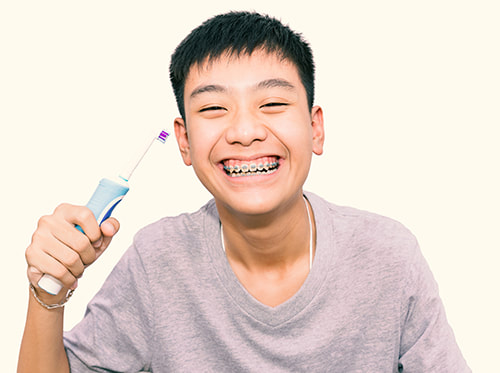 Smiling asian boy with braces holding electric toothbrush